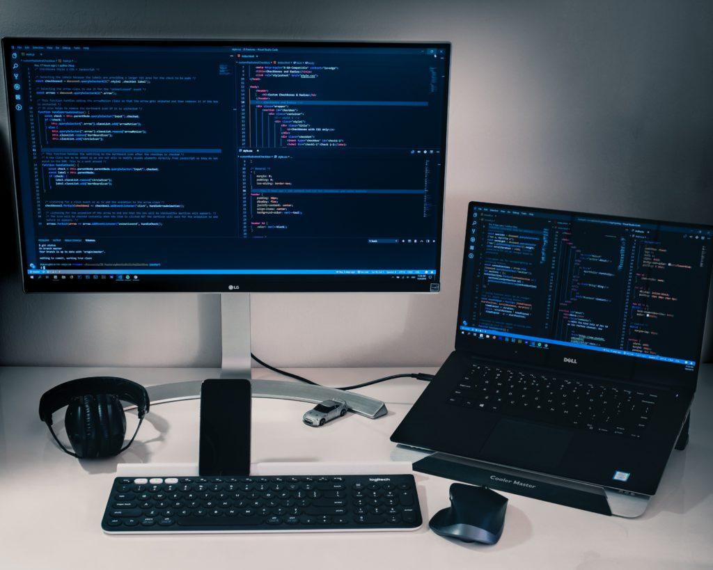 Ein Schreibtisch mit einem Monitor, einem Laptop und Arbeitsmaterial. Auf dem Bildschirm ist Programmcode zu sehen.